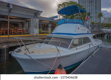 Honolulu, Hawaii, USA.  Apr. 18, 2019.  Restored 1950's cabin cruiser with the Waikiki Yacht Club in the background.