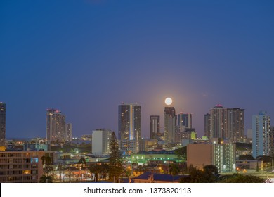 Honolulu, Hawaii, USA.  Apr. 19, 2019.  Nearly full Spring moon setting above downtown at an hour before dawn.