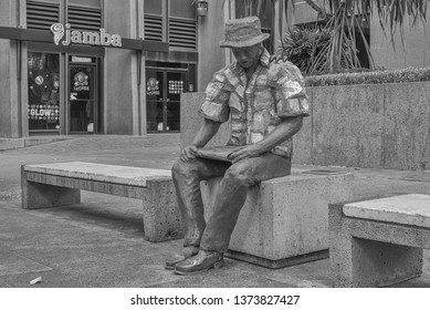 Honolulu, Hawaii, USA.  Apr. 19, 2019.  Statue of a man on a bench waiting for a bus and reading the Honolulu Newspaper.