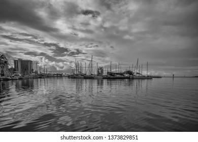 Honolulu, Hawaii, USA.  Apr. 19, 2019.  Monochrome dawn at the Ala Wai Harbor in Waikiki with tropical rain clouds above.