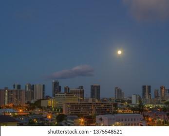 Honolulu, Hawaii, USA.  Apr. 20, 2019.  Before dawn in the Maliki District as a full moon sets.