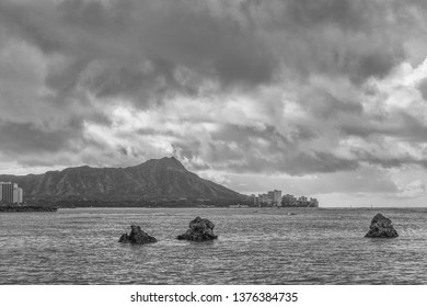 Honolulu, Hawaii, USA.  Apr. 21, 2019.  A Trio of coral heads above the water at low tide in Waikiki with Diamond Head and hotels in the background.