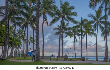 Honolulu, Hawaii, USA.  Apr. 22, 2019.  Waikiki sunrise as asian honeymoon tourists explore the beach scene.