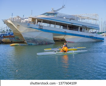 Honolulu, Hawaii, USA.  Apr. 22, 2019.  Outrigger canoe paddlers pass a sinking ship in Waikiki at the Ala Wai Harbor as fuel spill continues.