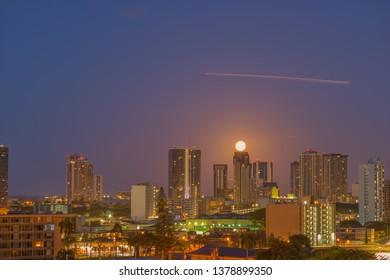 Honolulu, Hawaii, USA.  Apr. 24, 2019.  Moonset above the Financial District as an airplane streaks across the sky.