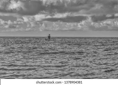 Honolulu, Hawaii, USA.  Apr. 24, 2019.  Trade wind morning in Waikiki as a female outrigger canoe paddler enjoys the Ala Moana Channel.