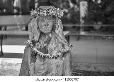 Honolulu, Hawaii, USA, April 25, 2016:  Vintage bronze hula dancer with flower leis and point of focus on the face.