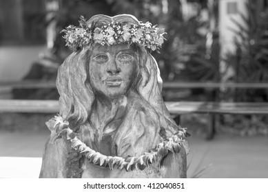 Honolulu, Hawaii, USA, April 27, 2016:  Portrait of a bronze hula maiden with flower leis.