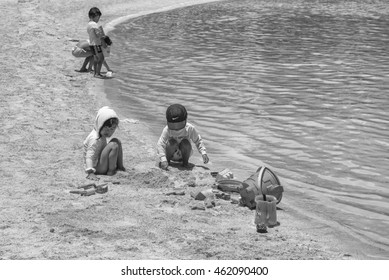 Honolulu, Hawaii, USA, August 1, 2016:  Young children playing in the sand at the lagoon in black and white.