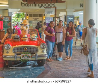 Honolulu, Hawaii, USA, August 1, 2017:  Ladies on a shopping excursion at the new Ala Moana Shopping Center with a restored car in the backdrop.