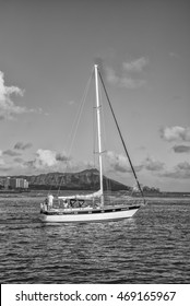 Honolulu, Hawaii, USA, August 15, 2016:  Sailboat and crew leaving the Ala Wai Harbor for a cruise to Waikiki with Diamond Head Crater and hotels in the background.