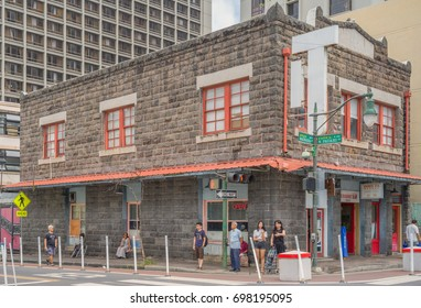 Honolulu, Hawaii, USA, August 18, 2017:  Chinatown street photograph of shoppers around an old building with newer skyscrapers in the background.