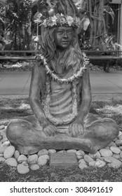 Honolulu, Hawaii, USA, August 21, 2015:  Life-size bronze Hula Girl with fresh flowers on display in Waikiki.  Hula is popular in the Hawaiian Islands.