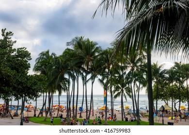 Honolulu, Hawaii, USA - Dec 15, 2015: Waikiki Beach and visitors, near the Kuhio Beach Hula Mound. This image also features a dramatic sky.