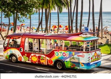 Honolulu, Hawaii, USA - Dec 15, 2015: Waikiki tourist shuttle bus along Kalakaua Ave, near Kuhio Beach Hula Mound, Waikiki Beach. This is an affordable form of transport and is popular among tourists.