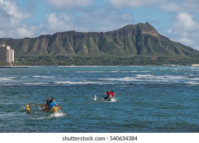 Honolulu, Hawaii, USA, Dec. 21, 2016:  Hawaiian Outrigger Canoe Teams Paddling to Diamond Head Crater with tropical clouds in the backdrop.