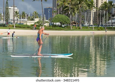 Honolulu, Hawaii, USA, Dec. 7, 2015:  Morning view of a woman exercising with a stand up paddle board at Waikiki Lagoon.  Stand up paddle boards are becoming popular in Honolulu.