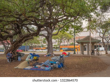 Honolulu, Hawaii, USA.  Feb. 25, 2019.  Homeless camp at Ala Moana Park with the luxury shopping center in the background.