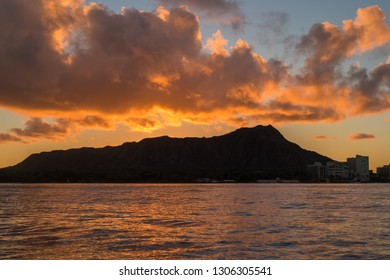 Honolulu, Hawaii, USA.  Feb. 6, 2019.  Red and gold dawn silhouetted on the ocean in Waikiki with Diamond Head in the background.