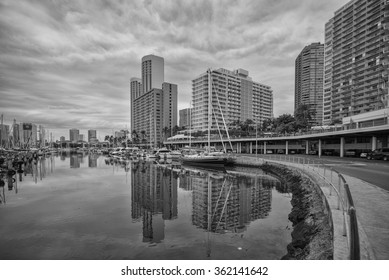 Honolulu, Hawaii, USA, Jan. 14, 2016:  Morning view of the Ilikai Dock and Hawaii Prince Resort at the Ala Wai Boat Harbor.  Storm clouds are signaling imminent rain.