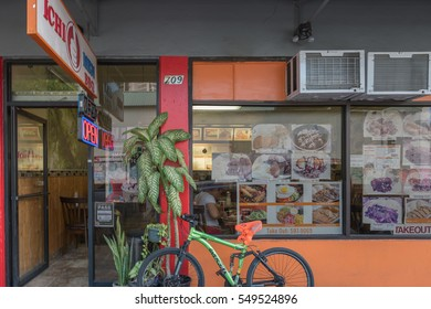 Honolulu, Hawaii, USA, Jan. 5, 2017:  Bright and colorful Waikiki plate lunch shop with a green bicycle parked in front.