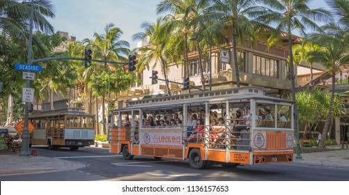 Honolulu, Hawaii, USA.  July 17, 2018.  Waikiki Trollies stuck in the endless Waikiki traffic  as tourists enjoy the view.