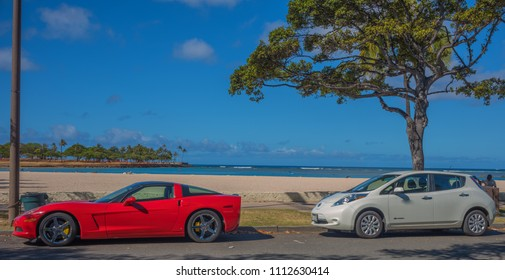 Honolulu, Hawaii, USA.  June 14, 2018.  Contrasting modes of beach transportation as a glass guzzling sports car parks in front of an electric vehicle.