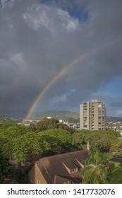 Honolulu, Hawaii, USA.  June 6, 2019.  Summer afternoon rainbow with tropical rain clouds over Manoa, Oahu.