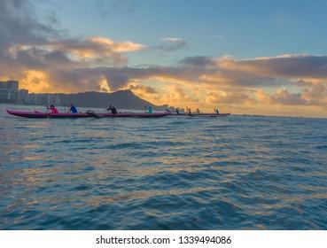 Honolulu, Hawaii, USA.  Mar. 15, 2019.  Sunrise Hawaiian outrigger canoe race as surfers watch with Diamond Head Crater in the backdrop.