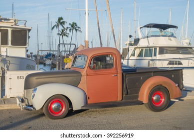 Honolulu, Hawaii, USA, March 17, 2016:   Morning side view of an antique pick up truck with boats from the Ala Wai Harbor in the background.