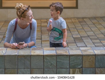 Honolulu, Hawaii, USA, March 7, 2018.  Ala Moana Shopping Center street photograph of a mother and son enjoying the view.