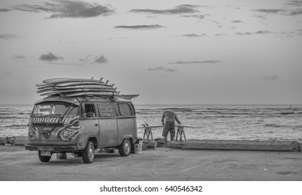 Honolulu, Hawaii, USA, May 15, 2017:  Dawn panorama of the Waikiki surf with the first surfer already preparing a surfboard for a day in the waves.