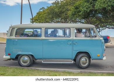 Honolulu, Hawaii, USA, May 27, 2017:  Vintage VW microbus/surf van at Ala Moana Beach Park with a Japanese wedding party aboard and parking for a photo session on the beach.