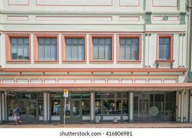 Honolulu, Hawaii, USA, May 7, 2016:  Morning sunlight reflecting off of a restored building in Honolulu Chinatown as business prepare to welcome customers.