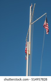 Honolulu, Hawaii, USA, Nov. 13, 2016:  Flags mounted on a sailing mast with clear blue sky background.