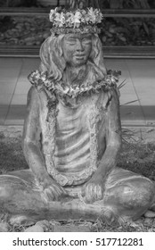Honolulu, Hawaii, USA, Nov. 18, 2016:  Black and white profile view of a hula girl cast in bronze and adorned with fresh Hawaiian flowers.
