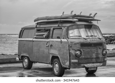 Honolulu, Hawaii, USA, Nov. 23, 2015:  Rainy morning view of an antique surfing van and old surfboards with Ala Moana Bowls surfing spot in the background.