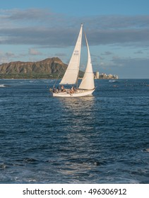 Honolulu, Hawaii, USA, Oct. 10, 2016:  Classic sloop sailing vessel and crew sailing through the waters of Waikiki with Diamond Head Crater in the background.
