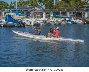 Honolulu, Hawaii, USA, Oct. 14, 2017:  Three young girls paddling a white and blue  outrigger canoe at the Waikiki Yacht Club.