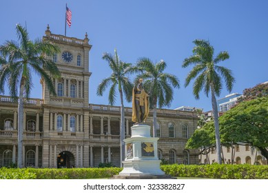 Honolulu, Hawaii, USA, Oct. 3, 2015:  The King Kamehameha Stature in downtown Honolulu with the Hawaii State Supreme Court Building in the background.  The fresh leis are for Aloha Week.