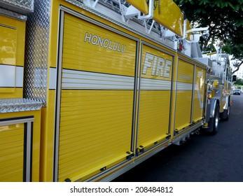 HONOLULU, HI - JULY 10, 2014: Side of yellow  Honolulu Fire Department Truck as it races down street to serve emergency situation.