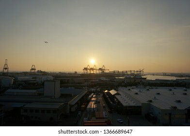 Honolulu - January 12, 2016: Aerial view of Sunset, Shipping Cranes, Matson Shipping Boat, and Airplane flying in the air on Oahu, Hawaii.