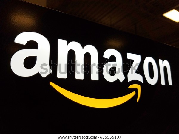 HONOLULU - JANUARY 12, 2017:  Amazon logo on black shiny wall in Honolulu Best Buy store.  Amazon is American international electronic commerce company. It's world's largest online retailer.