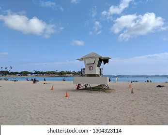 Honolulu - June 9, 2018:  Lifeguard Tower 1D and surfboard at Ala Moana Beach with people hanging out on a beautiful day.