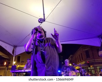 Honolulu -  March 17, 2017:  Man sings as Band plays on stage at St. Patrick's Day Block Party in street in Chinatown.