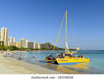 HONOLULU - MAY 11, 2012: A catamaran prepares for a sunset voyage at Waikiki Beach in May 2012.  Catamarans are a popular tourist activity at Waikiki Beach and offers a unique experience.