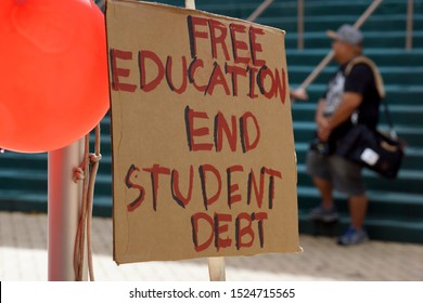 Honolulu - November 12, 2015:  Free Education End Student Debt Sign on the Campus of the University of Hawaii Manoa next to red balloons during protest of the cost of college.