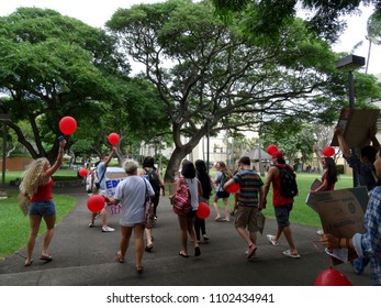 Honolulu - November 12, 2015:  Students march through Campus of the University of Hawaii Manoa holding red balloons protesting the cost of college.