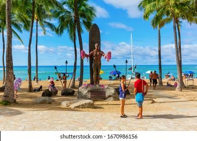 Honolulu, Oahu, Hawaii - November 04, 2019: Duke Kahanamoku statue at Waikiki beach with unidentified people. Kahanamoku is a legendary swimmer who popularized the ancient Hawaiian sport of surfing