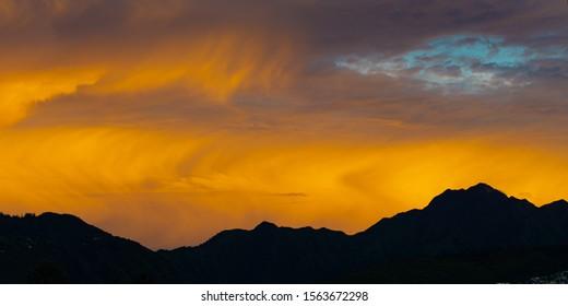 Honolulu sunrise vistas fro Kapiolani Park of the Honolulu cityscape and the Koolau Mountains vividly colored clouds and sky, mountain Silhouettes with orange sky